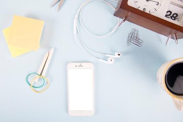 Smartphone en briefpapier in de buurt van klok en koffie