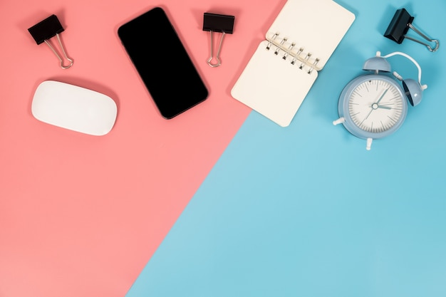 Smartphone en bureautoebehoren op kleurrijke achtergrond met exemplaarruimte. plat leggen.