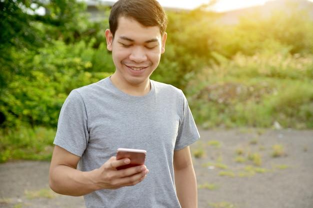 Smartphone en de glimlach van de mensenholding, mens die mobiele telefoon met behulp van