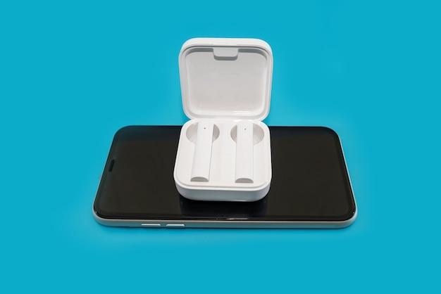 Smartphone en draadloze witte koptelefoon op een blauwe achtergrond.
