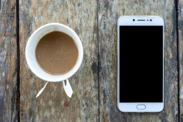 Smartphone en koffiekopje gemaakt van papier op oud houten bureau op bovenaanzicht.