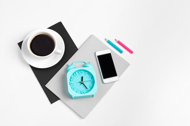 Smartphone en koffiekopje, kladblok close-up bovenaanzicht