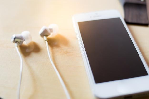 Smartphone en koptelefoon op houten achtergrond