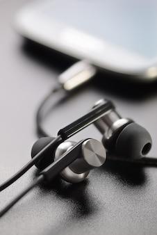 Smartphone en koptelefoon op tafel