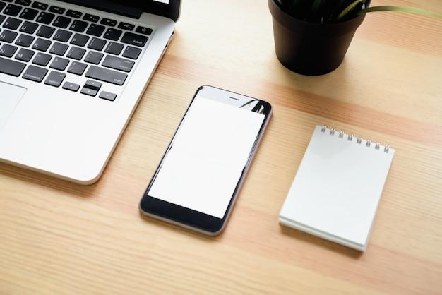 Smartphone en laptop op tafel in kantoorruimte, voor grafische weergave montage.