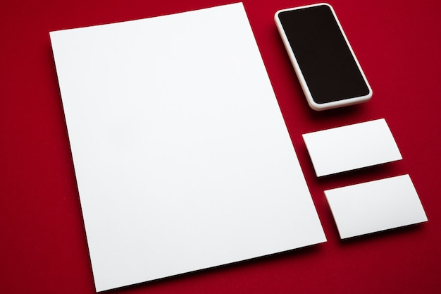 Smartphone en lege flyer posters en kaarten zwevend boven de rode achtergrond. moderne mockup in kantoorstijl voor reclame, afbeelding of tekst. lege witte copyspace voor ontwerp, zaken en financiënconcept.