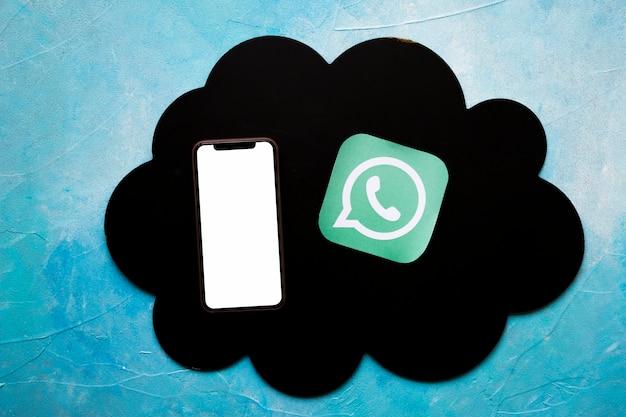 Smartphone en media pictogram op zwarte wolk boven de geschilderde blauwe muur