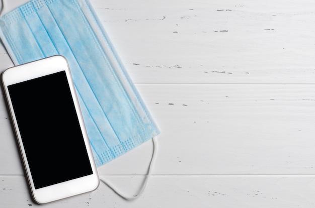 Smartphone en medisch masker op een wit