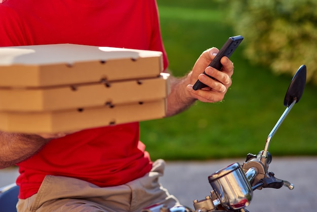Smartphone en pizzadozen in koeriershanden