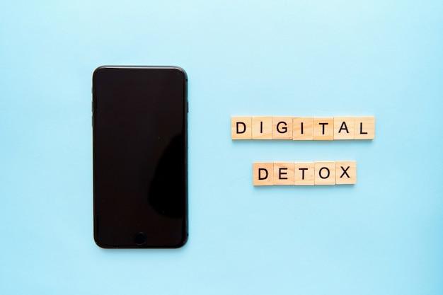 Smartphone en tekst digitale detox op blauwe ondergrond. social media verslaving