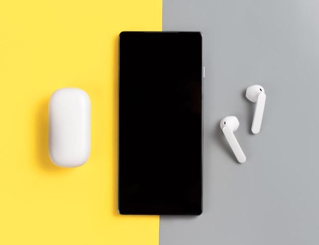 Smartphone en witte draadloze oortelefoons met het gevalbovenaanzicht op grijze en gele achtergrond