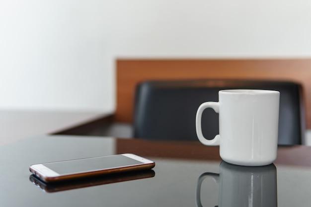 Smartphone en witte kop koffie op een tafel in café.