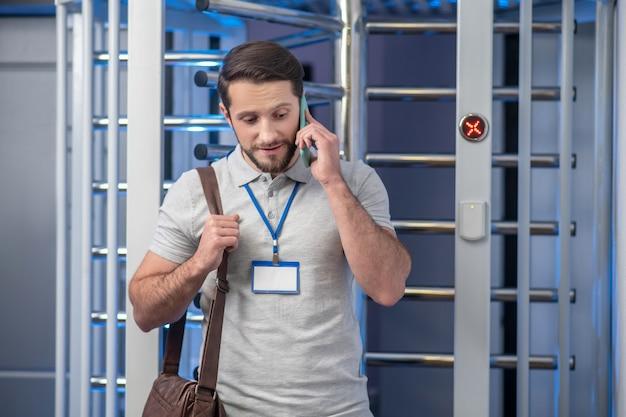 Smartphone, gesprek. jonge geïnteresseerde man met badge en tas staande praten over smartphone in de buurt van controlepost