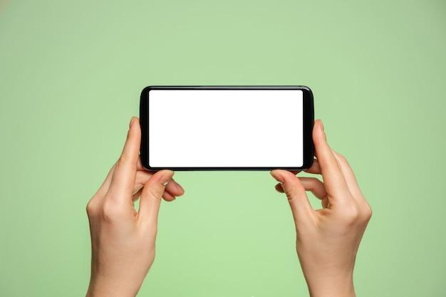 Smartphone horizontaal met een leeg scherm in de hand van een vrouw.