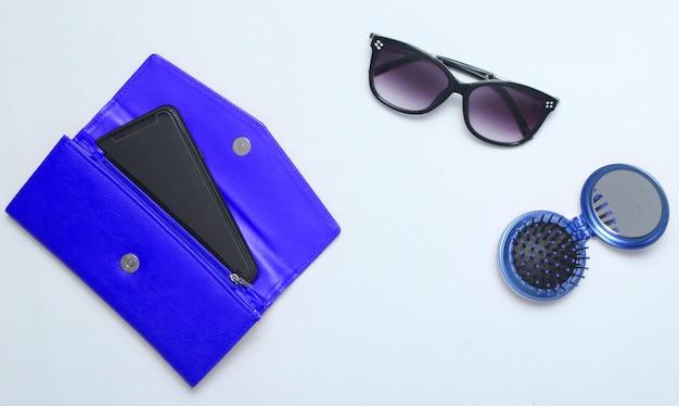 Smartphone in blauwe lederen portemonnee, zonnebril, spiegel haarborstel