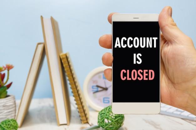Smartphone in de hand met het opschrift - accaunt is gesloten naast kantoorbenodigdheden