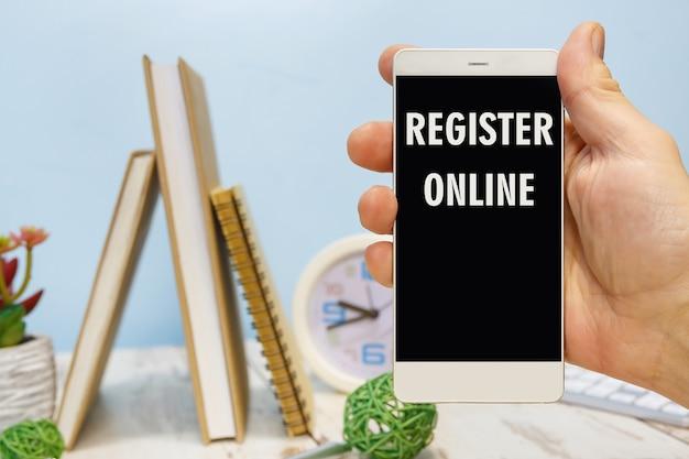 Smartphone in de hand met het opschrift register online naast kantoorbenodigdheden