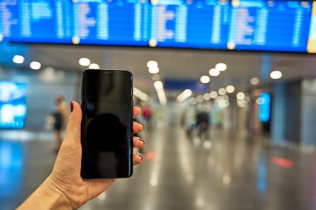 Smartphone in de hand tegen de achtergrond van het informatiebord op de luchthaven.