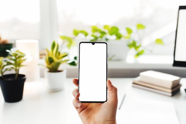 Smartphone in de hand, thuiswerken, kantoorspullen. hoge kwaliteit foto