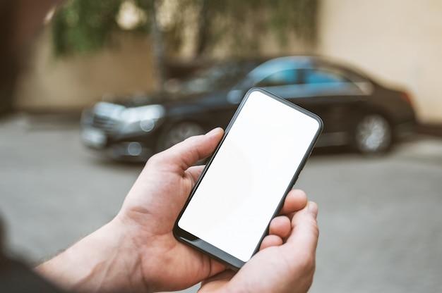 Smartphone in de hand van de man, op de achtergrond een zwarte auto.