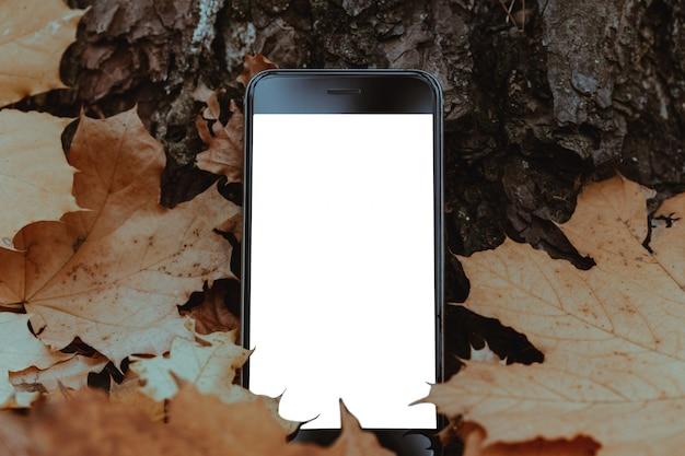 Smartphone in de herfstbladeren. mockup leeg wit telefoonscherm