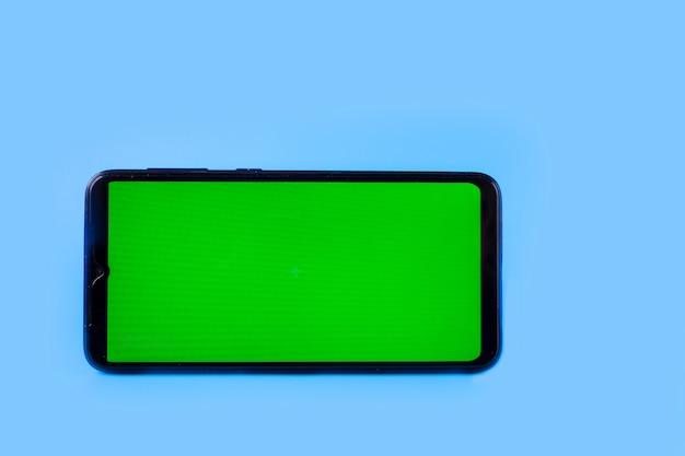 Smartphone in een horizontale positie met een groen scherm op een blauwe achtergrond, chroma key, mock up.