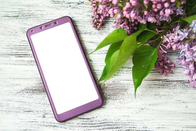 Smartphone in een lila omslag en lila bloemen