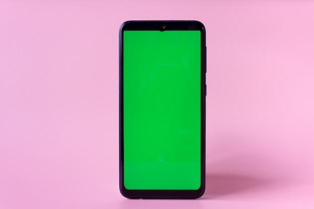Smartphone in een verticale positie met een groen scherm op een roze achtergrond, chroma key, mock up.