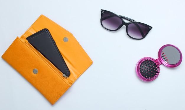 Smartphone in geel lederen portemonnee, zonnebril, spiegel haarborstel