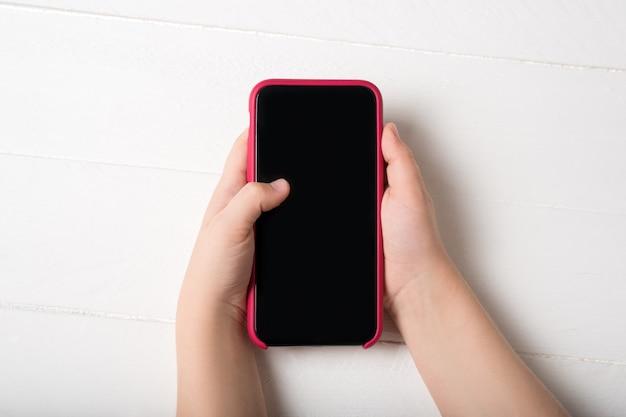 Smartphone in kinderhanden op een lichte achtergrond