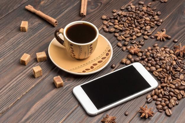 Smartphone, koffie drinken. koffiebonen verspreid over tafel, steranijs en stukjes bruine suiker.