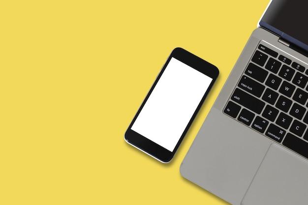 Smartphone leeg wit scherm met halve laptop op gele achtergrond. mockup mobiele telefoon leeg scherm.