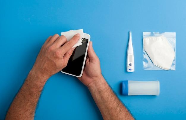 Smartphone, man's handen schoonmaken met witte doek, met masker in beschermende plastic zak,