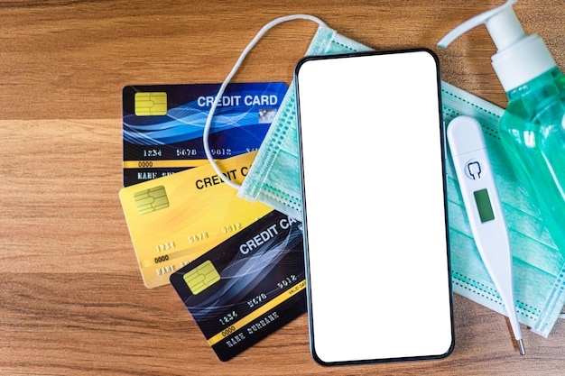 Smartphone met beschermend medisch wegwerpmasker, thermometer, creditcards en alcoholhanddesinfecterend middel op houten achtergrond