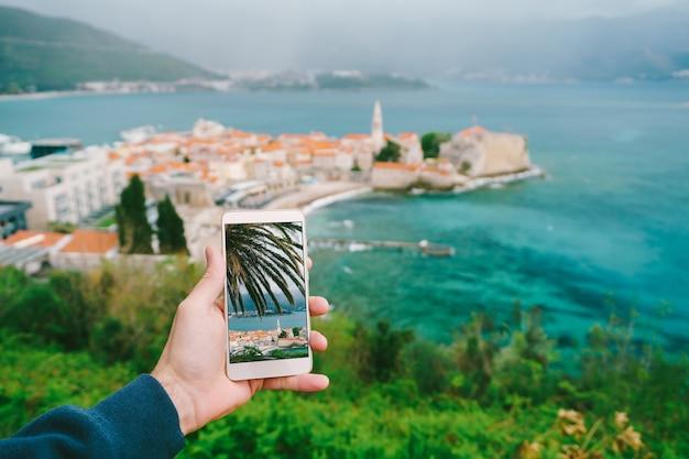 Smartphone met een foto van een palmboom op het scherm tegen het oppervlak van een oude stad