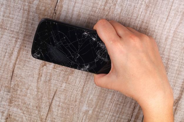 Smartphone met een gebroken scherm in de hand van het meisje