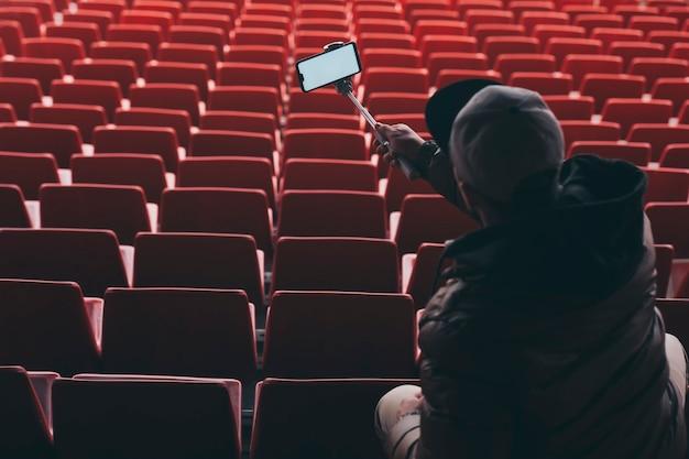 Smartphone met een selfiestok in de handenman