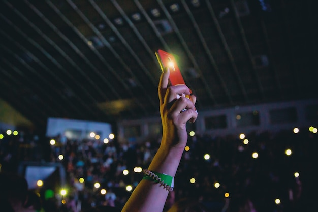 Smartphone met een zaklamp ingeschakeld in een vrouwelijke hand tijdens een concert