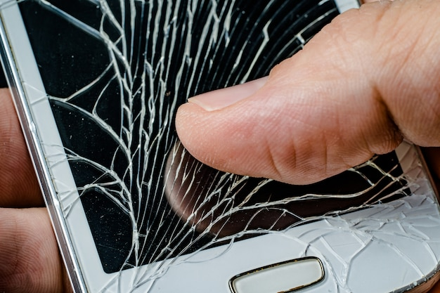 Smartphone met gebarsten display in de hand