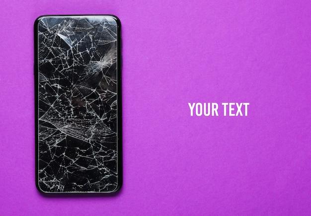 Smartphone met gebroken beschermend glas op paarse achtergrond. bovenaanzicht. kopieer ruimte