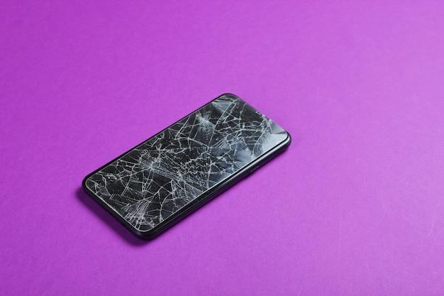 Smartphone met gebroken beschermend glas op paarse tafel.