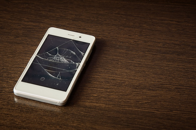 Smartphone met gebroken scherm op de houten tafel