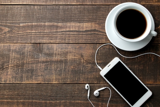 Smartphone met koptelefoon en een kopje koffie op een bruin houten tafel. uitzicht van boven