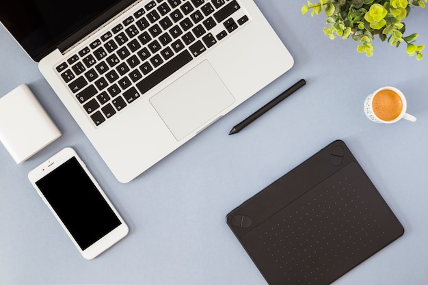 Smartphone met laptop, koffiekop en notitieboekje