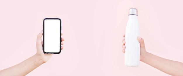 Smartphone met mockup in de hand en herbruikbare stalen thermo-waterfles in witte kleur, in de andere hand. achtergrond van pastel roze. panoramisch concept met kopie ruimte.