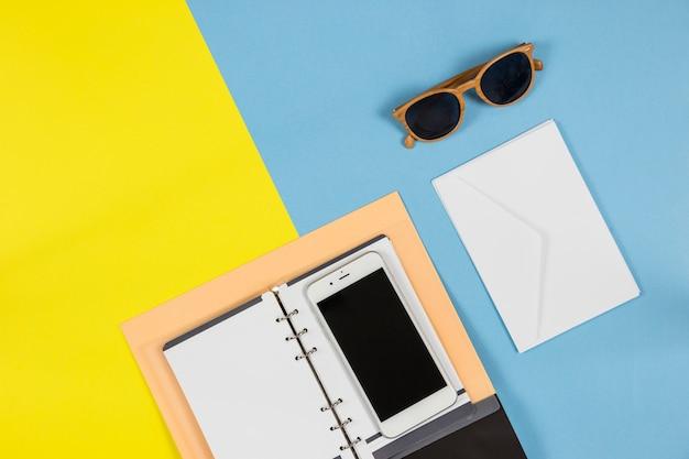 Smartphone met notitieboekje en envelop