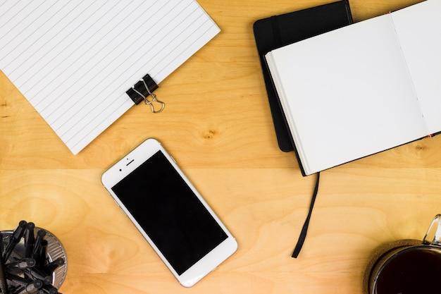 Smartphone met notitieboekje en koffiekop op lijst