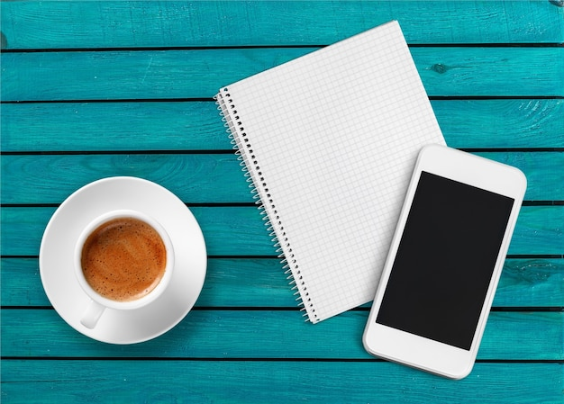 Smartphone met notitieboekje en kopje sterke koffie op houten achtergrond.