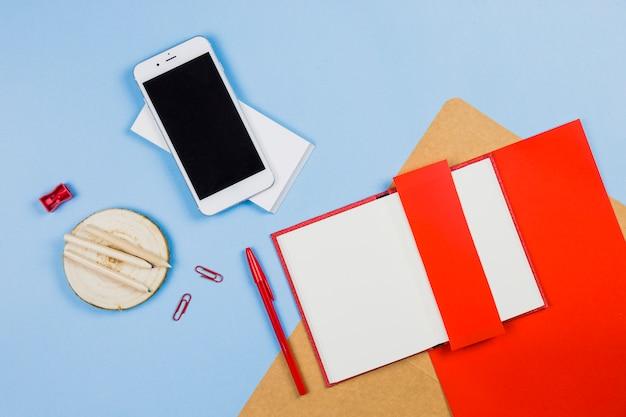 Smartphone met notitieboekje en potloden