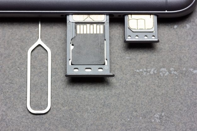 Smartphone met open sim-slots en micro sd-geheugen op een grijze achtergrond